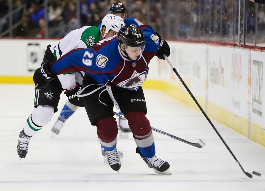 . Colorado Avalanche center Nathan MacKinnon (29) tries to move the puck down ice while being chased by Dallas Stars left wing Jamie Benn (14) during the first period Saturday, February 14, 2015 at the Pepsi Center in Denver, Colorado. (Photo By Brent Lewis/The Denver Post)