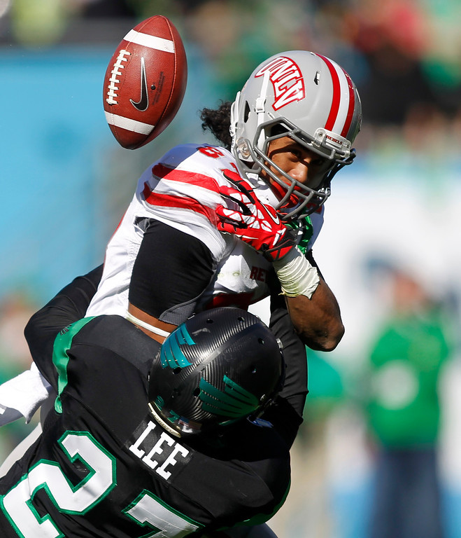 . North Texas defensive back Lairamie Lee (27) breaks up the pass intended for UNLV wide receiver Maika Mataele (87) during the first half of the Heart of Dallas NCAA college football game, Wednesday, Jan. 1, 2014, in Dallas. (AP Photo/Mike Stone)
