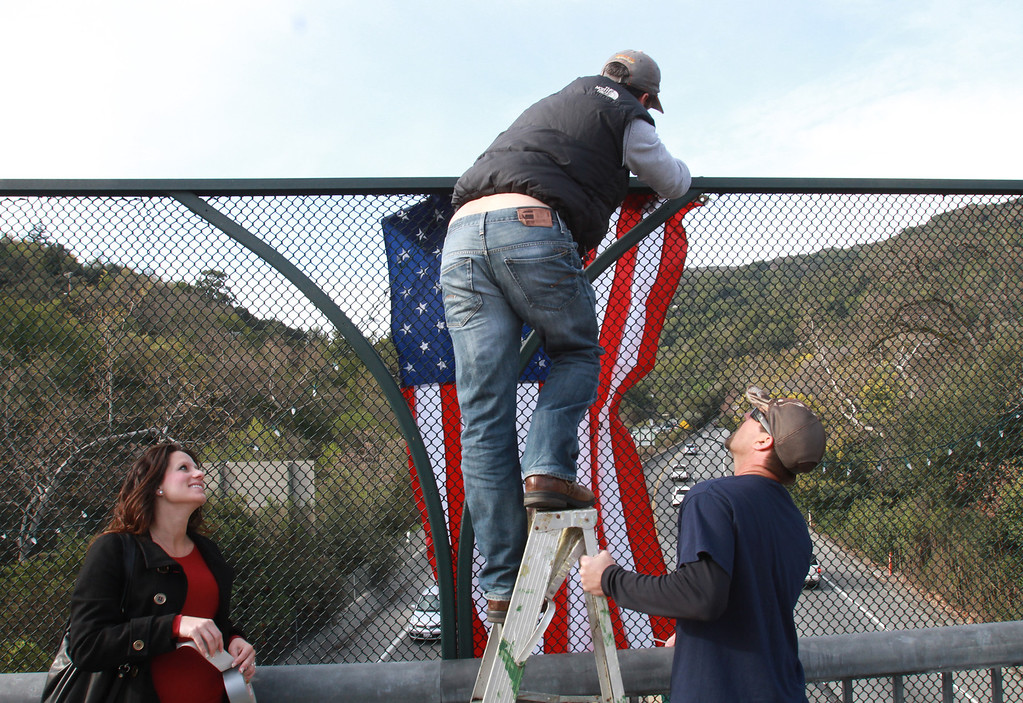 . San Jose firefighter Scott Fey hangs the American flag over the Main Street overpass in Los Gatos, Calif., in anticipation of the funeral procession for two slain Santa Cruz police officers as it makes its way to San Jose\'s HP Pavilion, and the funeral on March 7, 2013. (George Sakkestad/Bay Area News Group)