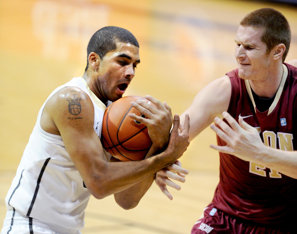. Xavier Talton of CU rips the ball from Ryley Beaumont of Elon during the second half of the December 13, 2013 game in Boulder. (Cliff Grassmick/Boulder Daily Camera)