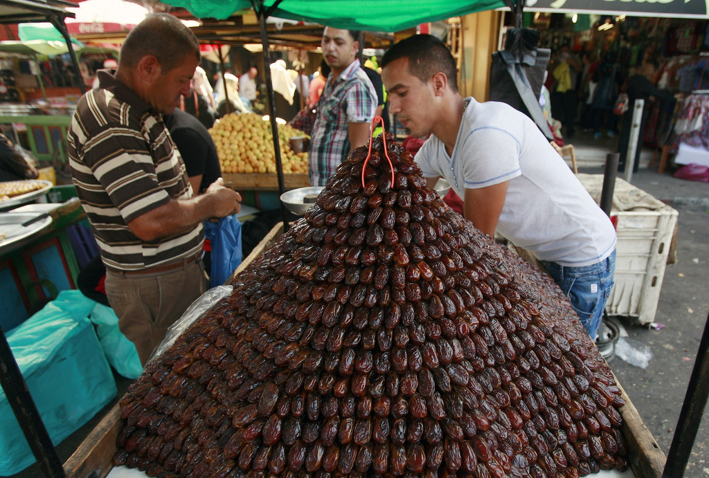 . A Palestinian vendor sells dates for Ramadan at a market in the West Bank city of Jenin ahead of Ramadan on Saturday, June 28, 2014. Muslims throughout the world are preparing themselves before the holy month of Ramadan, where observants fast from dawn till dusk. (AP Photo/Mohammed Ballas)