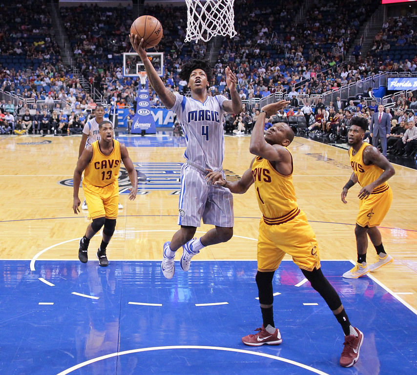 . Orlando Magic guard Elfrid Payton (4) shoots as he gets by Cleveland Cavaliers guard James Jones (1), center Tristan Thompson (13) and guard Iman Shumpert, right, during the first half of an NBA basketball game, Friday, Dec. 11, 2015, in Orlando, Fla. (AP Photo/John Raoux)