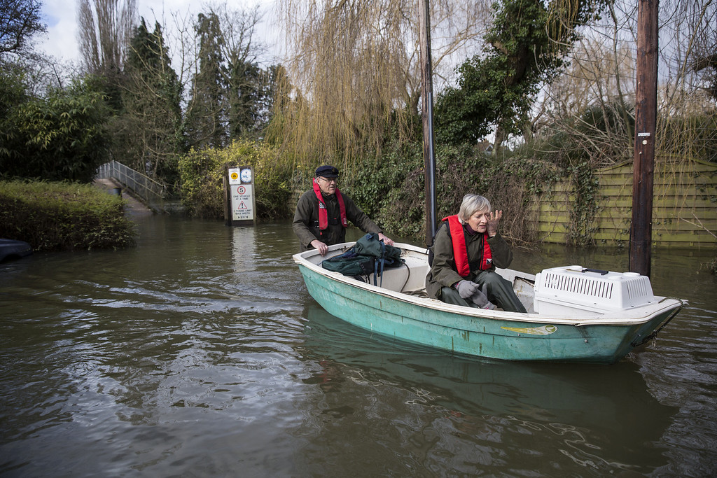 . A couple transport their cats to the vet by boat along a flooded road near the River Thames on February 13, 2014 in Wargrave, England.The Environment Agency continues to issue severe flood warnings for a number of areas on the River Thames in the commuter belt west of London. With heavier rains forecast for the coming week people are preparing for the water levels to rise. (Photo by Oli Scarff/Getty Images)