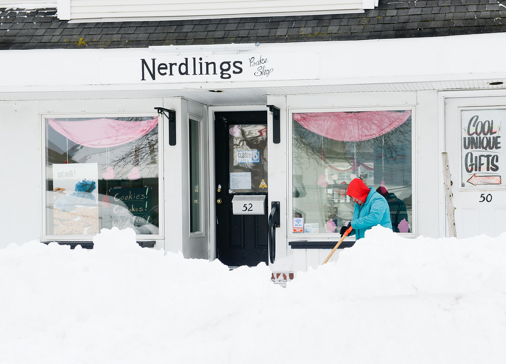. A woman shovels snow outside Nerdlings Bake Shop on January 27, 2015 in Sayville, New York.  Snow levels from winter storm Juno in New York have ranged from 7.8 inches in Central Park to more than 28 inches in Eastern Long Island. (Photo by Andrew Theodorakis/Getty Images)