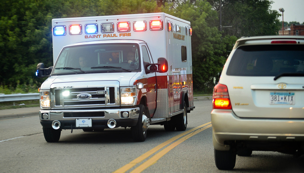 . An ambulance raced south on Rice Street from the scene in St. Paul near where law enforcement officers shot and apprehended shooting suspect Brian Fitch Sr., 39, on Wednesday. (Pioneer Press: Ben Garvin)