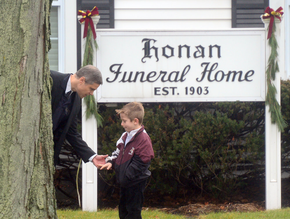 . A man speaks to his young son December 17, 2012 at the funeral for Jack Pinto, 6, one of the victims of the December 14, Sandy Hook elementary school shooting, in Newtown, Connecticut.  Funerals began Monday in the little Connecticut town of Newtown after the school massacre that took the lives of 20 small children and six staff, triggering new momentum for a change to America\'s gun culture.  AFP PHOTO/Emmanuel  DUNAND/AFP/Getty Images