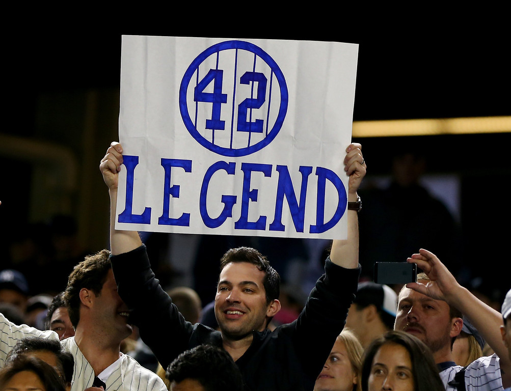 . NEW YORK, NY - SEPTEMBER 26:  Fans salute Mariano Rivera #42 of the New York Yankees after the game against the Tampa Bay Rays on September 26, 2013 at Yankee Stadium in the Bronx borough of New York City.  (Photo by Elsa/Getty Images)