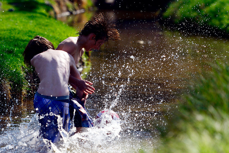 . Jack Maiocco, 14, tackles Tyler Maiocco, 13, in Smith\'s Ditch at Washington Park. Temperatures reached the low 80s in Denver. (Photo by AAron Ontiveroz/The Denver Post)