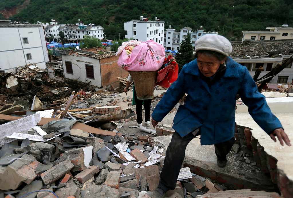 . Villagers walks through rubbles from destroyed houses following a massive earthquake in the town of Longtoushan in Ludian County in southwest China\'s Yunnan Province Tuesday, Aug. 5, 2014. (AP Photo/Andy Wong)