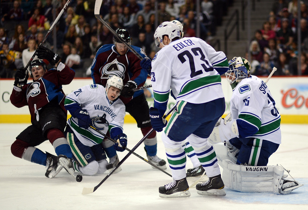 . DENVER, CO. - APRIL 13 : Alexander Edler of Vancouver Canucks (23) clears the puck in the 3rd period of the game against Colorado Avalanche at Pepsi Center. Denver, Colorado. April 13, 2013. Colorado won 4-3. (Photo By Hyoung Chang/The Denver Post)