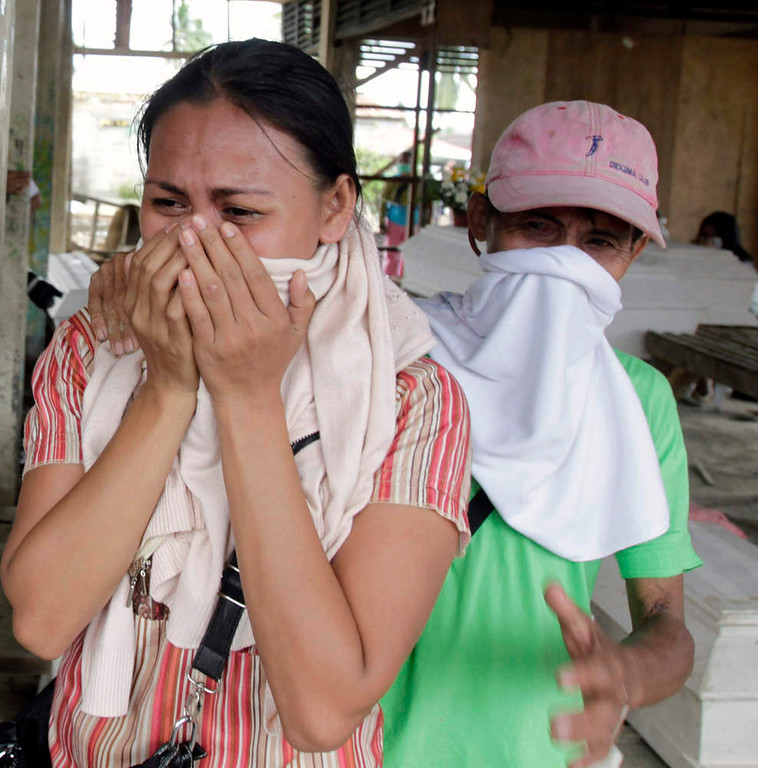. Residents cry while looking for their missing relatives amongst the coffins of typhoon Bopha victims lying at a destroyed market turned into a mortuary, in New Bataan town in Compostela Valley, southern Philippines December 8, 2012. Philippine President Benigno Aquino declared a state of national calamity on Saturday, four days after this year\'s strongest typhoon left nearly 1,000 people dead or missing mostly in the country\'s resource-rich south. REUTERS/Erik De Castro