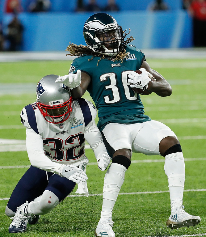 . Philadelphia Eagles\' Jay Ajayi, right, tries to get away from New England Patriots\' Devin McCourty during the first half of the NFL Super Bowl 52 football game Sunday, Feb. 4, 2018, in Minneapolis. (AP Photo/Matt York)