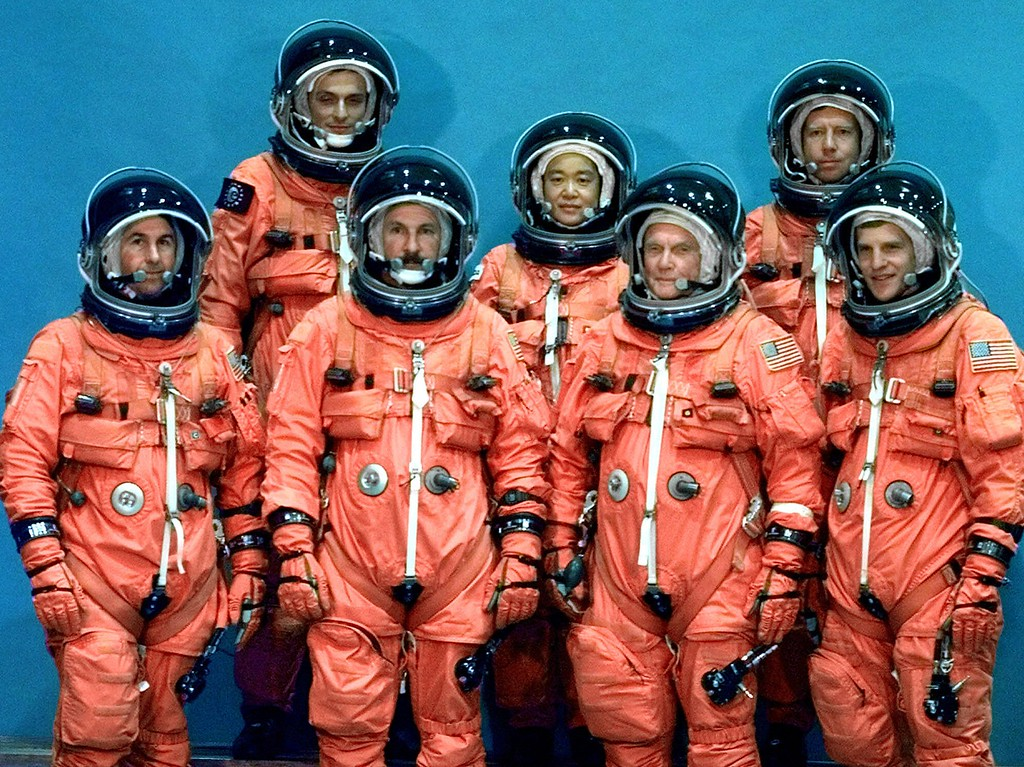 . Members of the space shuttle Discovery crew, from left to right, bottom row, Stephen Robinson, Curt Brown, John Glenn, Scott Parazynski, top row, Pedro Duque, Chiaki Mukai and Steven Lindsey pose for a photo Aug. 27, 1998 at Johnson Space  Center in Houston. (AP Photo/David J. Phillip)
