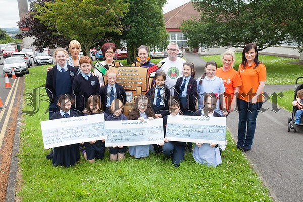 Pupils from St Malachy's ps Carnagat present cheque to Muscular Dystrophy, Multiple Selerosis and the Irish Pilgrimage Trust money raised through various activities held within the school. R1725057