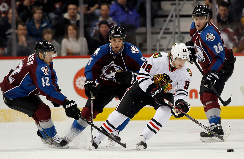 . Chicago Blackhawks right wing Patrick Kane, third from left, picks up a loose puck as Colorado Avalanche right wing Chuck Kobasew, far left, defenseman Shane O\'Brien, second from left, and center Paul Stastny cover in the first period of an NHL hockey game in Denver, Friday, March 8, 2013. (AP Photo/David Zalubowski)