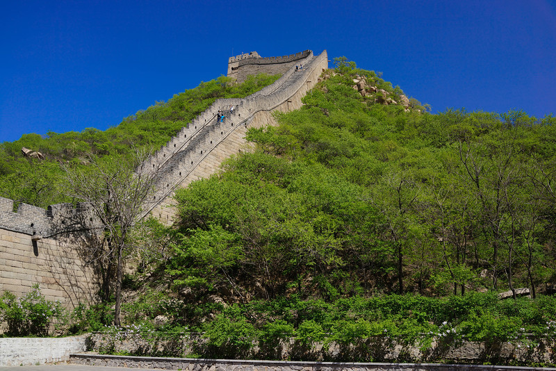 Great Wall of China near Badaling.  The Badaling Great Wall, constructed in 1502 (during the Ming Dynasty), once served as a crucial military fortification, and is now the most impressive and representative section of the striking Great Wall. It is located in Yanqing County, about 70 kilometers (43.4 miles) from the downtown area of Beijing. Twisting and turning at an altitude of 1,000 meters (3,281 feet), the Badaling Great Wall appears exceptionally lofty on the undulating mountains. It is an architectural marvel that has been praised by many leaders, from China and around the world. Both Richard Nixon and Margaret Thatcher visited this section of the wall, and in 1987 it was placed on the World Heritage List of UNESCO, a list reserved for destinations considered to have outstanding universal value.  As Badaling was once an important military strategy point, here the wall is comparatively high and firm. It has a length of 3,741 meters (2.3 miles) and it is equipped with dense watchtowers. The wall is about 8.5 meters (27.9 feet) high and slopes inward as it rises in height. The wall is 6.5 meters (21.3 feet) wide at its base, and its rim spans about 5.7 meters (18.7 feet) across. The wall's exterior is composed of large granite slabs that surround layers of loess and gravel. Its coping is made of large bricks that provide a smooth walkway, wide enough for ten people to easily walk side by side. A parapet on the coping once provided a defense barrier against assailants.  Crenellated battlements decorate the parapet's exterior. In the battlement, there are square holes, from which soldiers had an outlook and shot at the enemy. Two-storey castles lie approximately every 400 meters (about 1,312 feet) on the wall. The castle's second floor gave soldiers an additional advantage over attackers; the arched cavity below was used to store artillery and also doubled as a simple dormitory for the watchmen. A number of high beacon towers were built so that when the enemies invaded, signals could be sent out to call for reinforcement.  While the Badaling Great Wall has not served as a military fortification since the Qing Dynasty (1644-1911), it now hosts a number of modern attractions, including a Great Wall Museum and a Great Wall Cinema. The museum and cinema both provide information about the history and culture of the Great Wall.  Source: http://www.beijingtrip.com/attractions/greatwall/badaling.htm  Map: http://www.beijingtrip.com/attractions/greatwall/images/beijing-badaling-map.jpg