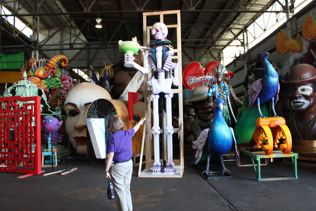 A woman stands in front of parade floats at Mardi Gras World