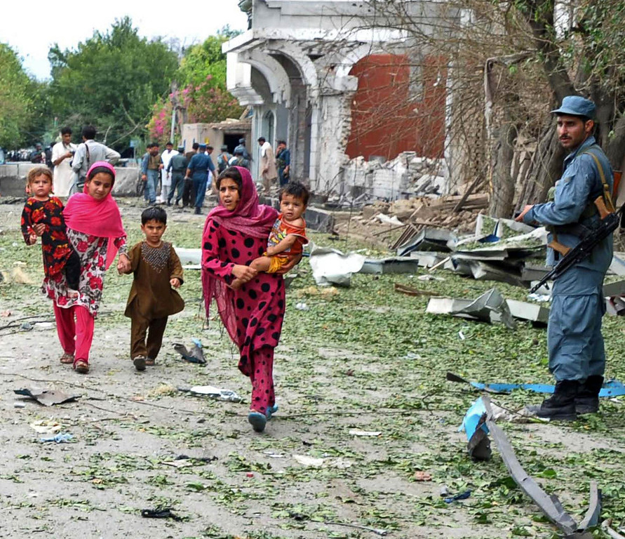 . An Afghan policeman looks on as children flee from the site of a suicide attack in front of the Indian consulate in Jalalabad on August 3, 2013. Suicide bombers targeted the Indian consulate in the eastern Afghan city of Jalalabad, killing at least eight civilians when they detonated an explosives-packed car outside the building.    Noorullah Shirzada/AFP/Getty Images