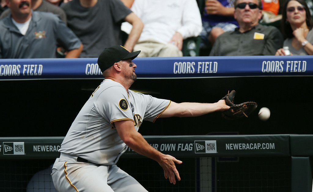 . Pittsburgh Pirates first baseman Gaby Sanchez fails to pull in a foul ball off the bat of Colorado Rockies\' Josh Rutledge in the third inning of a baseball game in Denver, Sunday, July 27, 2014. (AP Photo/David Zalubowski)