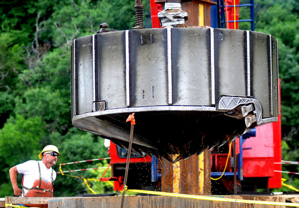 . A worker on the work platform for Pier 12 watches Monday, July 22, 2013 as a 200-foot crane maneuvers a huge drill bit into a shaft that will guide it to the river bottom to drill into the bedrock to make room for the footings for the new St. Croix River bridge. (Pioneer Press: John Doman)