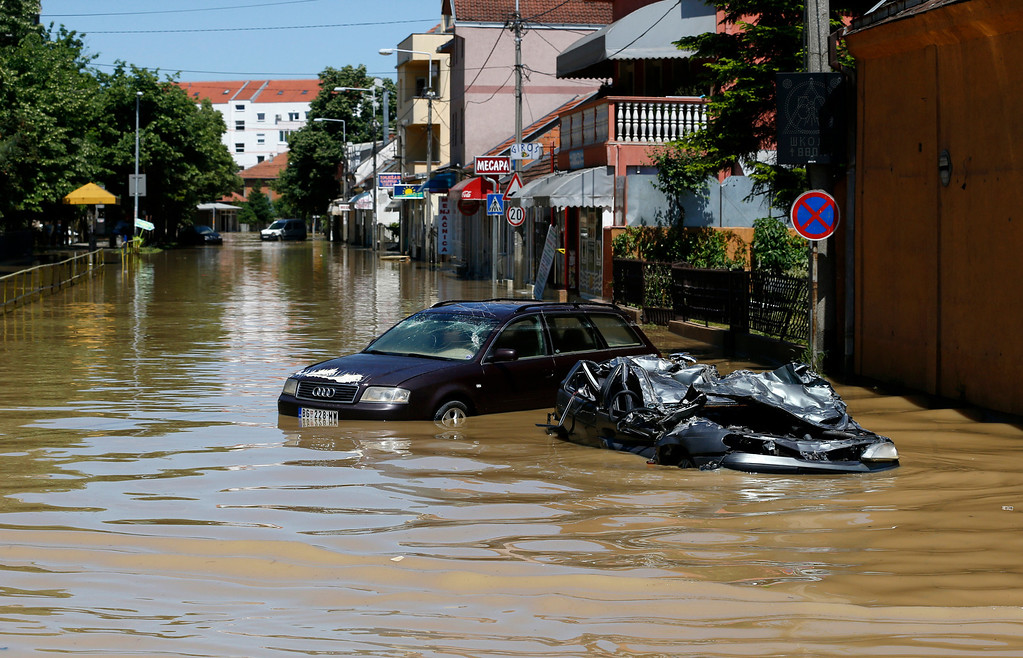 . A severely damaged car  stands in a flooded street in Obrenovac, some 30 kilometers (18 miles) southwest of Belgrade, Serbia, Monday, May 19, 2014. Belgrade braced for a river surge Monday that threatened to inundate Serbia\'s main power plant and cause major power cuts in the crisis-stricken country as the Balkans struggle with the consequences of the worst flooding in southeastern Europe in more than a century. (AP Photo/Darko Vojinovic)