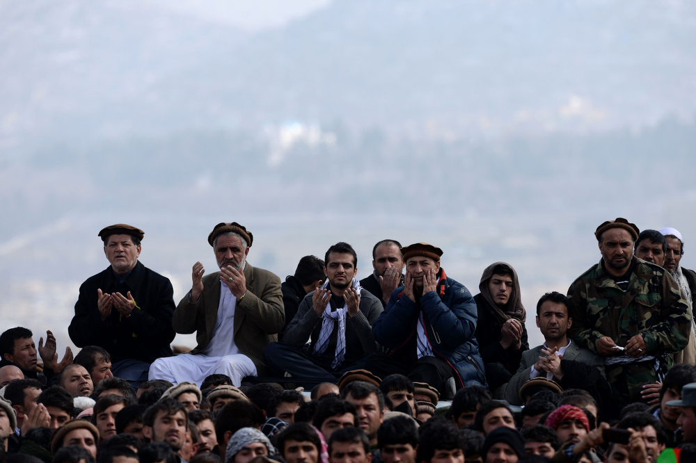 . Afghan officials and relatives offer prayers towards the unseen coffin of Afghan Vice-President Marshal Mohammad Qasim Fahim, formerly one of the country\'s most feared warlords, during his funeral on a hilltop in Kabul on March 11, 2014. (WAKIL KOHSAR/AFP/Getty Images)