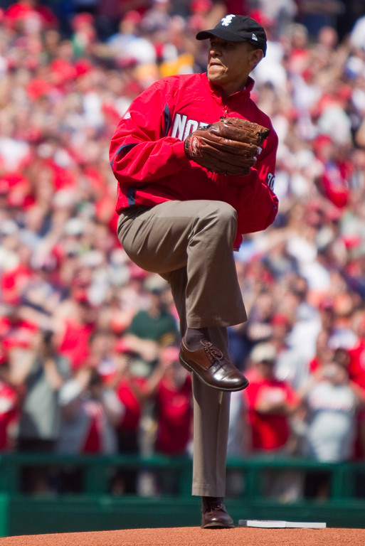 . Wearing a Washington Nationals jacket and a Chicago White Sox hat, President Barack Obama delivers the first pitch of the Washington Nationals home opening baseball game against the Philadelphia Phillies, Monday, April 5, 2010, at Nationals Park in Washington. (AP Photo/Evan Vucci)