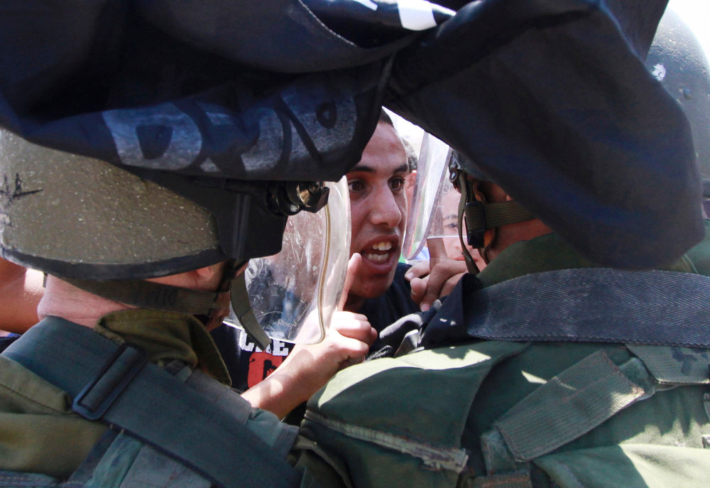 ". A Palestinian protester argues with Israeli border policemen during a rally to commemorate the 1948 creation of the Israel state known in Arabic as the ""Nakba Day\"", or \""Day of the Catastrophe\"" outside the West Bank town of  Bethlehem, Tuesday, May 14, 2013. (AP Photo/Nasser Shiyoukhi)"
