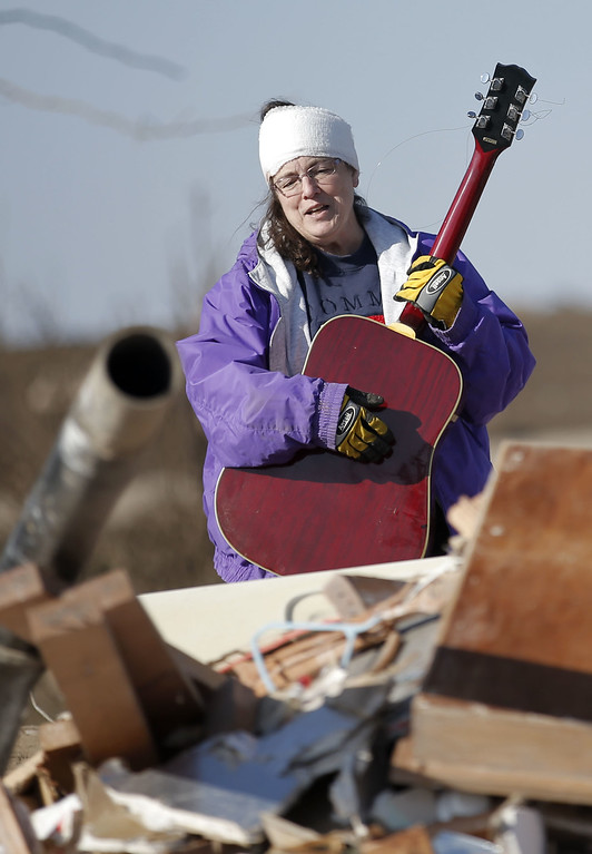 . Candy Trudell finds a guitar in the wreckage of her home on IL-64 after a tornado swept through the previous night, on April 10, 2015 in Rochelle, Illinois. According to reports, 11 people were injured and one person was killed when tornadoes and thunderstorms passed through the northwestern suburbs of Chicago. (Photo by Jon Durr/Getty Images)
