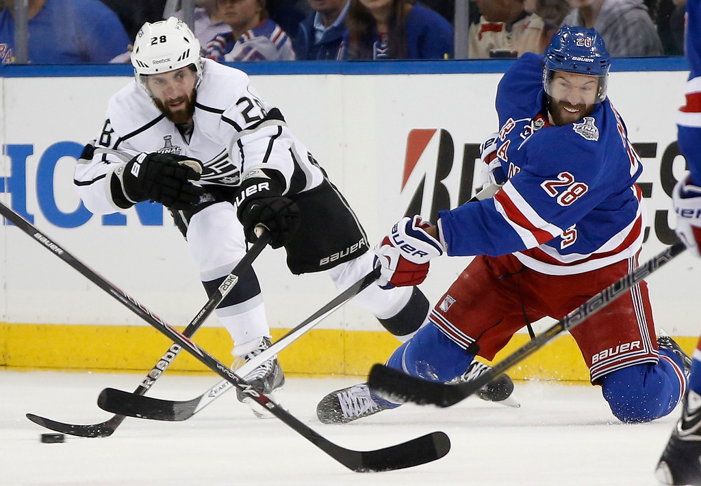 . New York Rangers center Dominic Moore (28), right, passes off the puck against Los Angeles Kings center Jarret Stoll (28) in the first period during Game 3 of the NHL hockey Stanley Cup Final, Monday, June 9, 2014, in New York. (AP Photo/Kathy Willens)