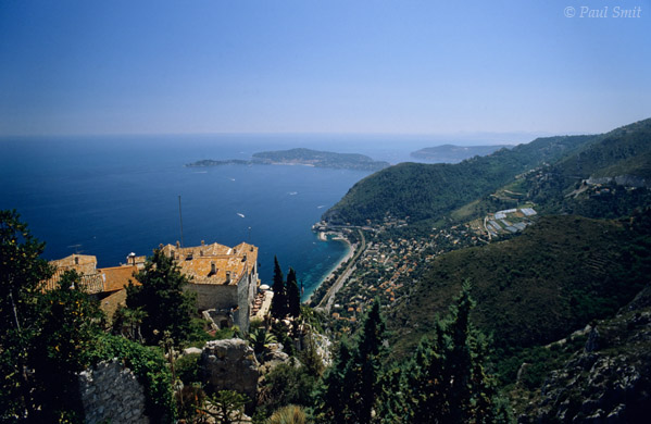 [FRANCE.COTEDAZUR 2648]  'Eze above the Côte.'  From a distance Eze is the most enchanting 'village littoral' of the Côte d'Azur. Here its roofs are seen from the Exotic Garden, with the Cap Ferrat peninsula in the distance. But every other building is a souvenir or antiques shop, coffeehouse or ice cream vendor. Photo Paul Smit.
