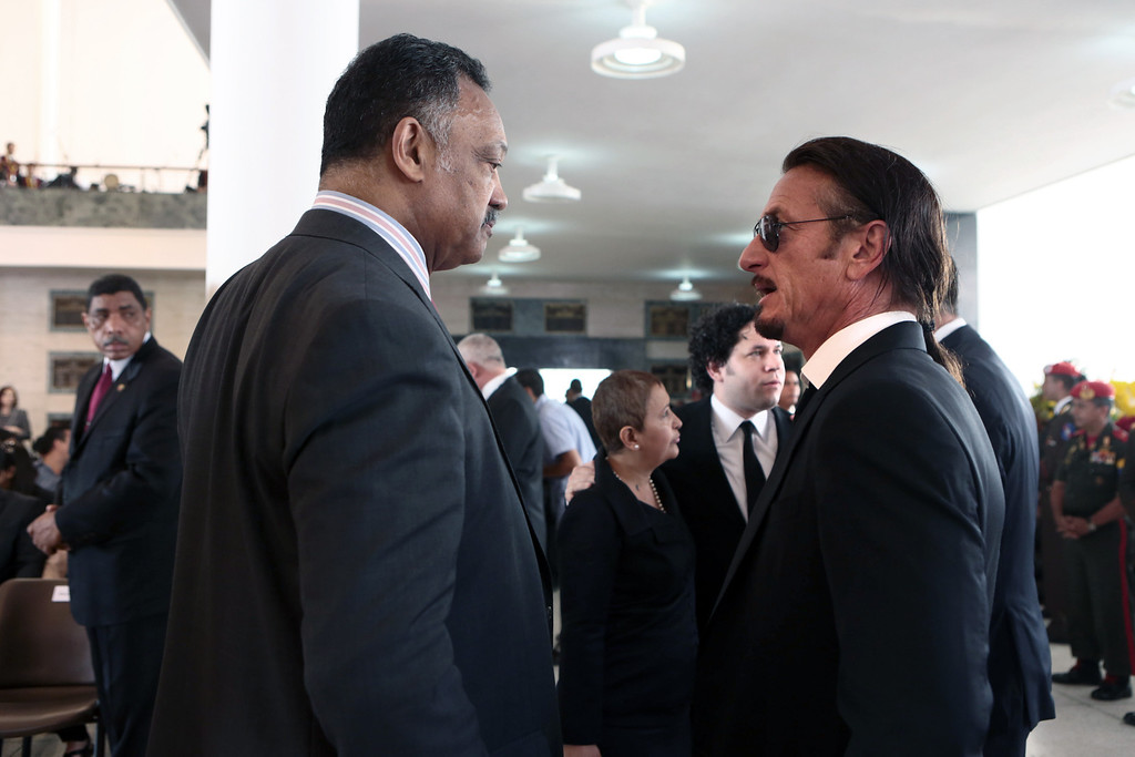 . Handout picture released by the Venezuelan presidency showing US Reverend Jesse Jackson (L) talking with US Actor and filmmaker Sean Penn during the funeral of Venezuelan President Hugo Chavez, in Caracas, on March 8, 2013.    AFP PHOTO/PRESIDENCIA/HO