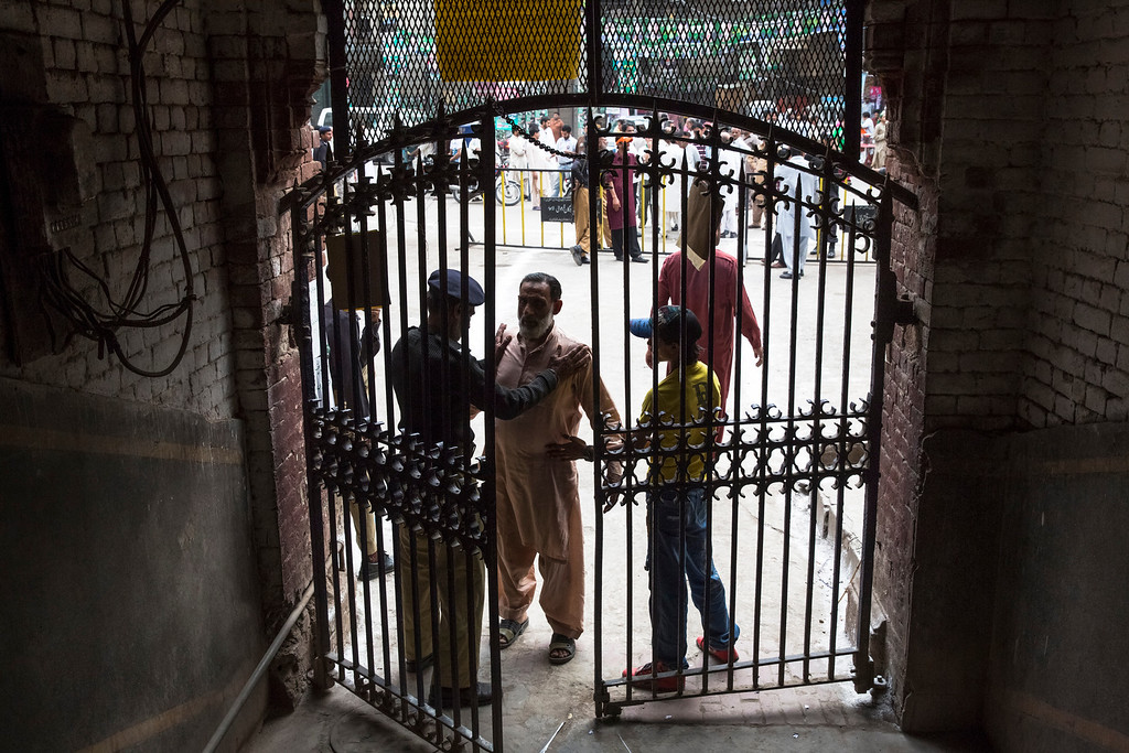 . LAHORE, PAKISTAN - MAY 11: A Pakistani police oficer searches a man on entry at a polling station on May 11, 2013 in the Old City of Lahore, Pakistan. Millions of Pakistanis cast their votes in parliamentary elections; the first time in the country\'s history that an elected government will hand over power to another elected government.   (Photo by Daniel Berehulak/Getty Images)