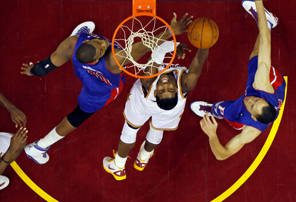 . Cleveland Cavaliers\' Kyrie Irving, center, shoots against Detroit Pistons\' Greg Monroe, left, and Tayshaun Prince in an NBA basketball game Tuesday, Feb. 21, 2012, in Cleveland. (AP Photo/Mark Duncan)