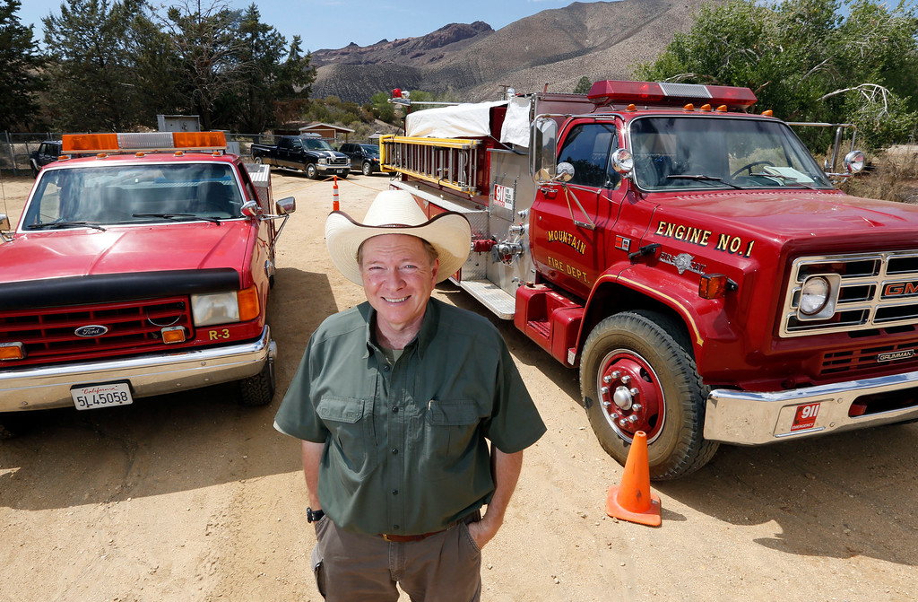 . Leo Grilloposes with two of his firefighting rigs at his DELTA (Dedication & Everlasting Love to Animals) Rescue complex in Acton, Calif.  Aug. 29, 2013. (AP Photo/Reed Saxon)