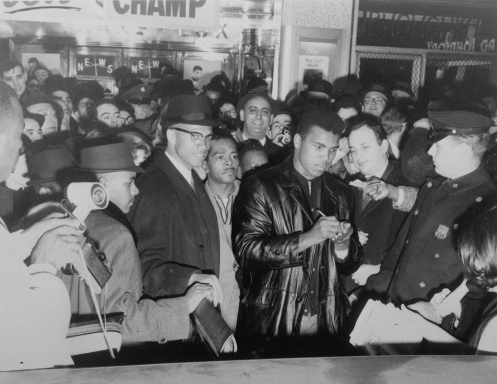 . World heavyweight boxing champion, Cassius Clay, signs autographs outside the Trans-Lux Theater on Broadway at 49th Street, New York City, March 1, 1964, after he had watched a screening of the films showing his title victory over Sonny Liston in Miami Beach, February 25.  On Clay\'s left, with hat and glasses looking at the camera, is Malcolm X, a leader in the Black Muslim movement.  (AP Photo)