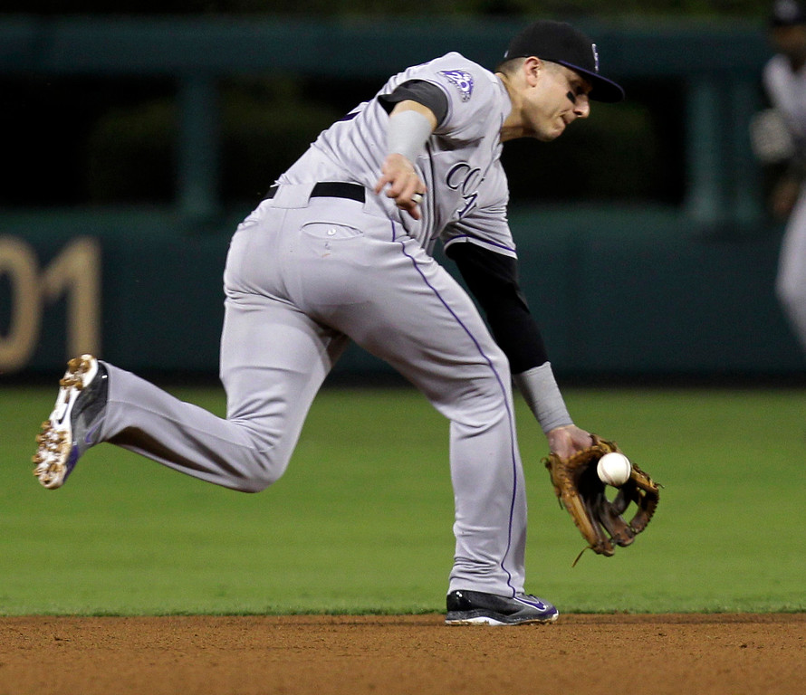 . Colorado Rockies shortstop Troy Tulowitzki bobbles the ball on a hit by Philadelphia Phillies\' Carlos Ruiz in the fourth inning in a baseball game, Thursday, Aug. 22, 2013, in Philadelphia. (AP Photo/Laurence Kesterson)