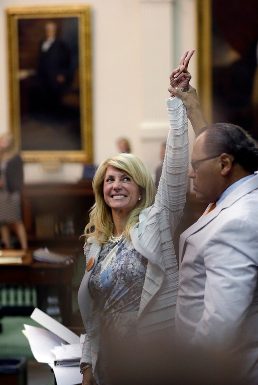 . Sen. Wendy Davis, D-Fort Worth, left, who tries to  filibuster an abortion bill, reacts as time expires, Tuesday, June 25, 2013, in Austin, Texas. Amid the deafening roar of abortion rights supporters, Texas Republicans huddled around the Senate podium to pass new abortion restrictions, but whether the vote was cast before or after midnight is in dispute. If signed into law, the measures would close almost every abortion clinic in Texas.  (AP Photo/Eric Gay)