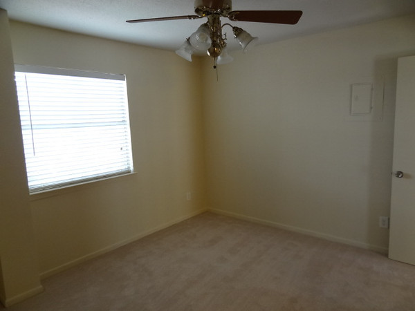 A view inside the freshly painted master bedroom reveals the new just-installed carpeting.