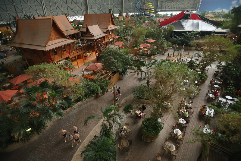 . Visitors walk among the Thai House (L) and other restaurants at the Tropical Islands indoor resort on February 15, 2013 in Krausnick, Germany. Located on the site of a former Soviet military air base, the resort occupies a hangar built originally to house airships designed to haul long-distance cargo. Tropical Islands opened to the public in 2004 and offers visitors a tropical getaway complete with exotic flora and fauna, a beach, lagoon, restaurants, water slide, evening shows, sauna, adventure park and overnights stays ranging from rudimentary to luxury. The hangar, which is 360 metres long, 210 metres wide and 107 metres high, is tall enough to enclose the Statue of Liberty.  (Photo by Sean Gallup/Getty Images)