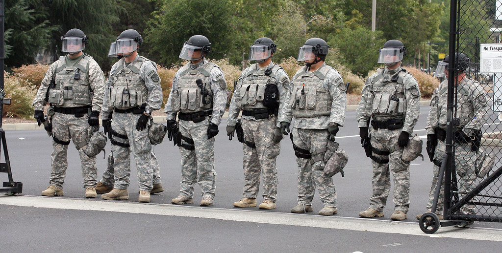 . Lawrence Livermore Laboratory protective force officers block the entrance during a protest in Livermore, Calif., on Tuesday, Aug. 6, 2013. The event marked the 68th anniversary of the atomic bombings of Hiroshima and Nagasaki during WWII.  (Jim Stevens/Bay Area News Group)