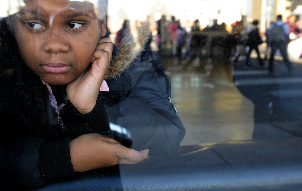. From a window at  the Hollywood Barber Shop, 10-year-old Malayah Goodloe watches the  Martin Luther King Jr. Marade  as it winds along E. Colfax Ave. on it\'s way downtown.  The marade, march/parade,  started at the MLK statue in the City Park  on Monday, January 21, 2013.   (Photo By Cyrus McCrimmon / The Denver Post)