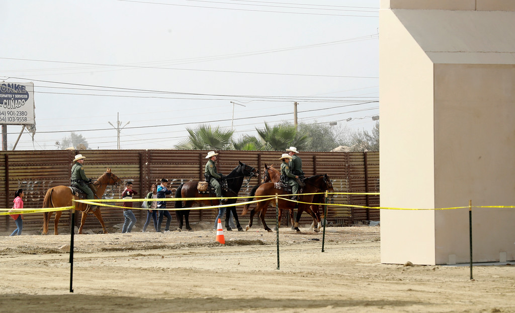 . A group of people are detained by Border Patrol agents on horseback after crossing the border illegally from Tijuana, Mexico, near prototypes for a border wall, right, are being constructed Thursday, Oct. 19, 2017, in San Diego. Companies are nearing an Oct. 26 deadline to finish building eight prototypes of President Donald Trump\'s proposed border wall with Mexico. (AP Photo/Gregory Bull)