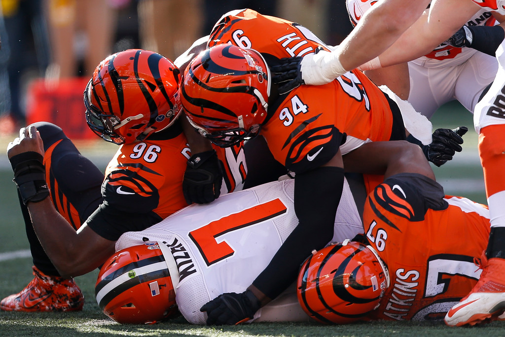 . Cleveland Browns quarterback DeShone Kizer (7) is tackled by Cincinnati Bengals defensive end Chris Smith (94), defensive end Carlos Dunlap (96), defensive tackle Geno Atkins (97) in the first half of an NFL football game, Sunday, Nov. 26, 2017, in Cincinnati. (AP Photo/Gary Landers)