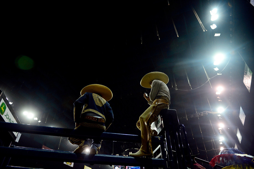 . Salvador Martinez (left) and  Santiago Guadarrama watch the action National Western Stock Show\'s Mexican Rodeo Extravaganza at the Denver Coliseum on Sunday, Jan. 13, 2013. AAron Ontiveroz, The Denver Post