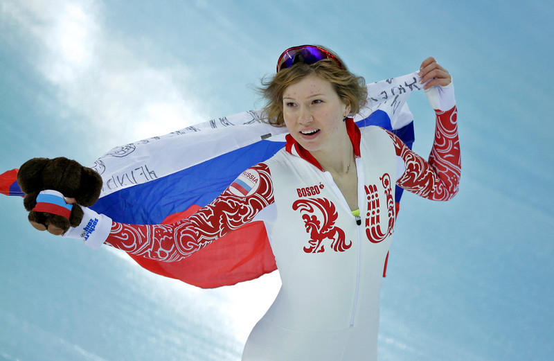 . Silver medalist Russia\'s Olga Fatkulina holds her national flag and celebrates after the women\'s 500-meter speed skating at the Adler Arena Skating Center during the 2014 Winter Olympics, Tuesday, Feb. 11, 2014, in Sochi, Russia. (AP Photo/David J. Phillip )
