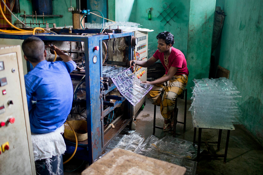". Bangladeshi work in a plastic packet manufacturing factory in Dhaka, Bangladesh, Monday, June 4, 2018. The theme for this year\'s World Environment Day, marked on June 5, is ""Beat Plastic Pollution.\"" (AP Photo/A.M. Ahad)"
