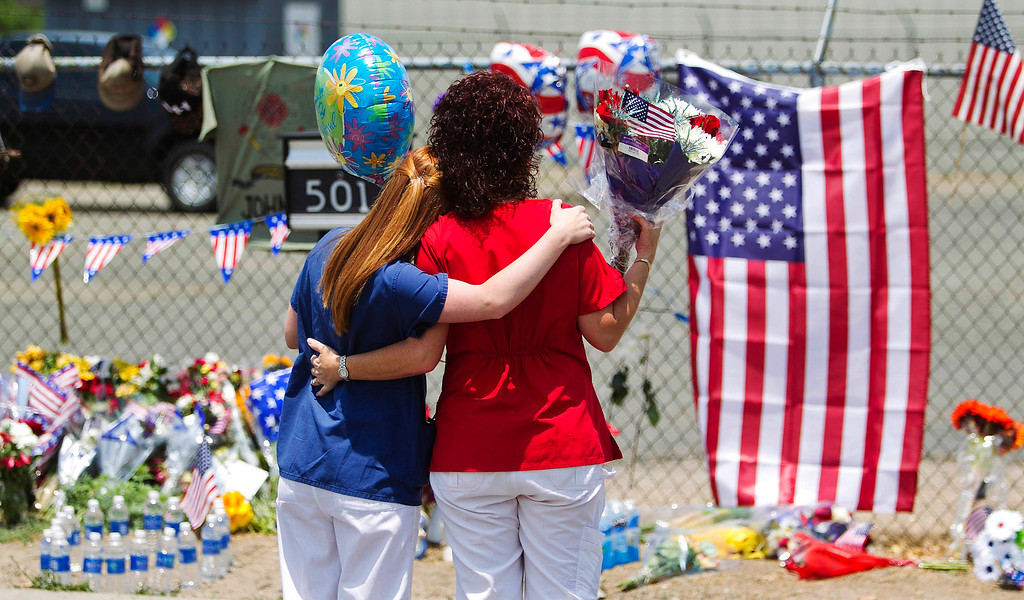 . Carianne Sarvar, left, and Kathy Stapp, look over a makeshift memorial at the fire station Monday, July 1, 2013, in Prescott, Ariz., where an elite team of firefighters was based. Sarvar said her child attends the same daycare as one of the children of the fallen firefighters. (AP Photo/The Arizona Republic, Patrick Breen)