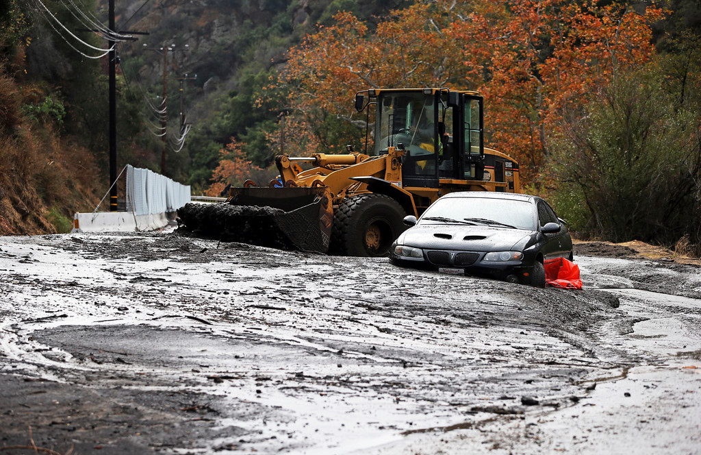 . A bulldozer operator begins to clear a car trapped in a deep debris flow that covered parts of Topanga Canyon Boulevard near the village of Topanga west of Los Angeles, Tuesday, Jan. 9, 2017. Multiple people were killed and homes were swept from their foundations as mud and debris from wildfire-scarred hillsides flowed through neighborhoods and onto a key Southern California highway Tuesday during a powerful winter storm that dropped record rain across the state. (AP Photo/Reed Saxon)