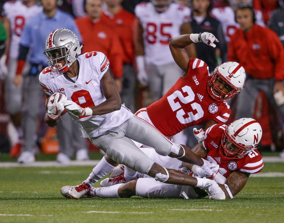 . Ohio State wide receiver Binjimen Victor (9) is tripped up by Nebraska defensive back Dicaprio Bootle (23) and defensive back Lamar Jackson (21) during the first half of an NCAA college football game in Lincoln, Neb., Saturday, Oct. 14, 2017. (AP Photo/Nati Harnik)